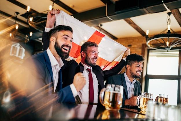 Les fans d'hommes d'affaires crient et regardent le football à la télévision et boivent de la bière dans un pub