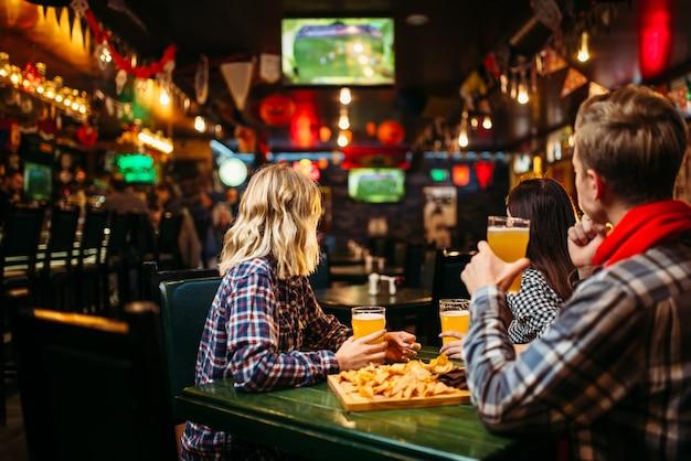 Fans regardant match et boit de la bière au bar des sports