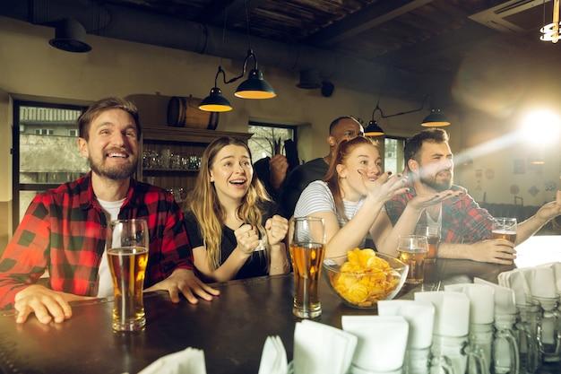Les fans de sport applaudissent au bar-pub et boivent de la bière pendant la compétition de championnat