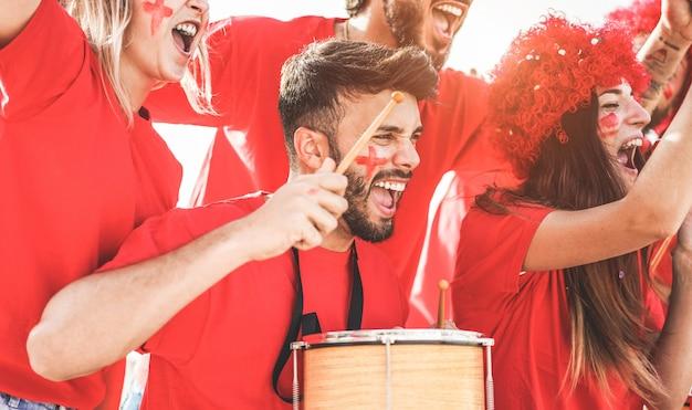 Les fans de sport rouges crient tout en soutenant leur équipe hors du stade