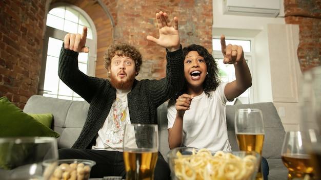 Fantastique. couple excité, amis regardant un match de sport, championnat à la maison. amis multiethniques, fans acclamant leur équipe sportive préférée