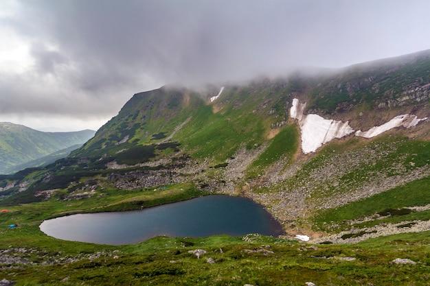 Fantastique large vue paisible du lac bleu dans la vallée verte et de petites tentes touristiques à la montagne rocheuse avec des plaques de neige recouvertes de nuages bas. beauté de la nature, du tourisme et du concept de voyage.