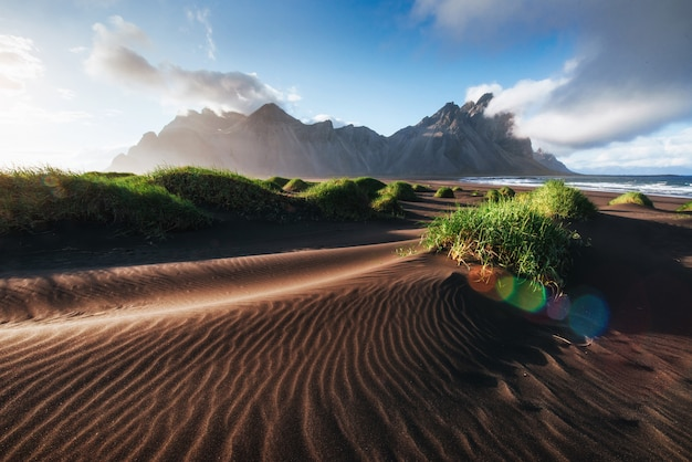 Fantatique à l'ouest des montagnes et des dunes de sable volcaniques sur la plage de stokksness, en islande. matin d'été coloré islande, europe
