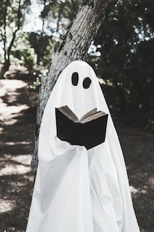 Fantôme appuyé sur un arbre et livre de lecture