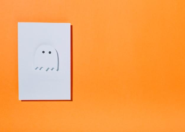 Fantôme blanc avec de petits yeux sur une feuille de papier