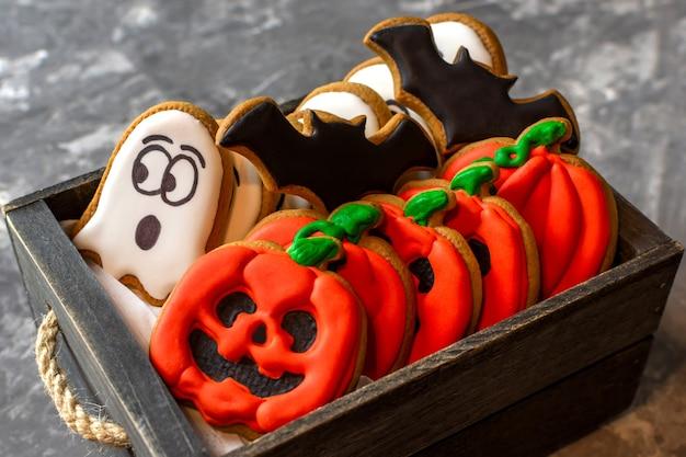 Fantôme de citrouille d'halloween en pain d'épice dans une boîte en bois sur un espace de copie de fond en pierre sombre