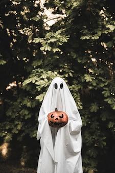 Fantôme tenant une citrouille sombre près de la brousse