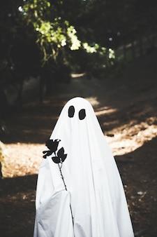 Fantôme tenant une rose noire dans un parc