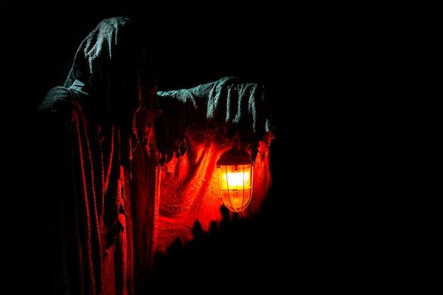 Le fantôme tient une lanterne allumée sur une horreur de fond sombre