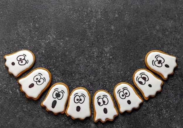 Fantômes blancs d'halloween de pain d'épice sur l'espace de copie de fond de pierre sombre