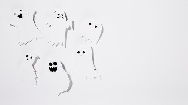 Des fantômes d'halloween en papier avec des grimaces