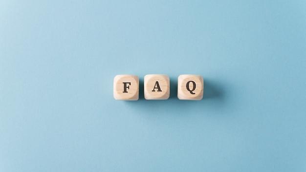 Faq sur l'orthographe de trois dés en bois sur fond bleu clair.