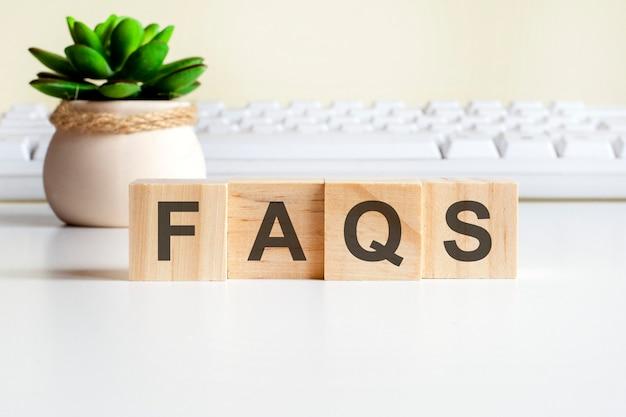 Faqs mot fait avec des blocs de bois. concepts de vue de face, plante verte dans un vase à fleurs et clavier blanc sur fond