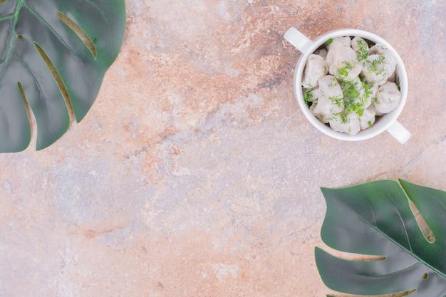Farce khinkal caucasien dans un bol avec des herbes hachées sur le dessus.