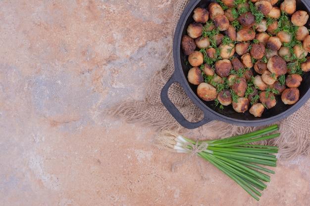 Farce à la viande grillée dans une poêle noire aux herbes