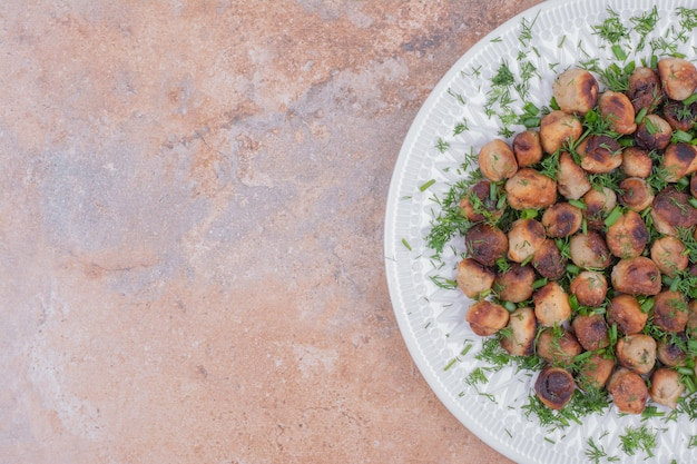 Farce à la viande servie dans une assiette blanche aux herbes