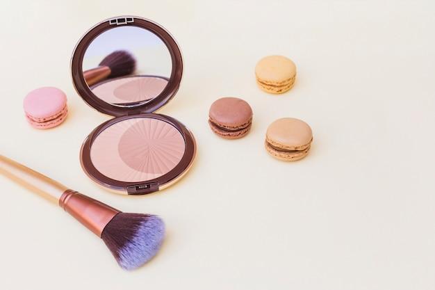 Fard à joues avec macaron et pinceau de maquillage sur fond beige