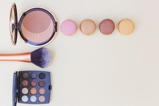 Fard à joues avec macaron; pinceau de maquillage et palette de fard à paupières sur fond beige