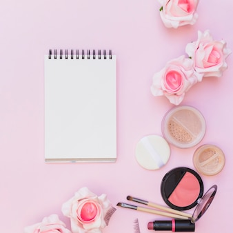 Fard à joues; rouge à lèvres; éponge; pinceau de maquillage avec des roses sur fond rose