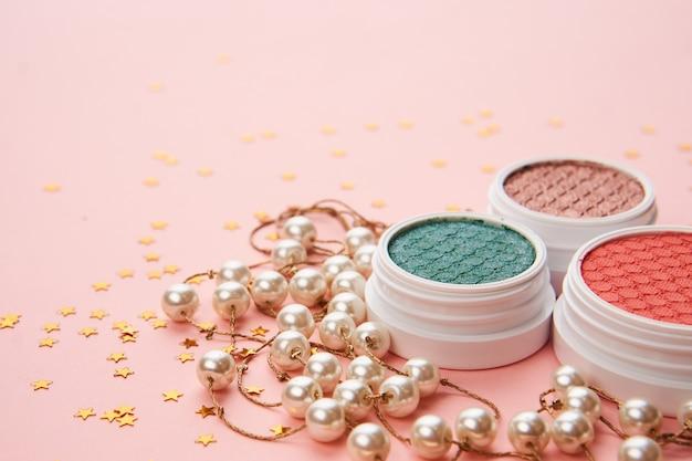 Fard à paupières accessoires perles maquillage pinceaux collection cosmétiques professionnels et fond rose