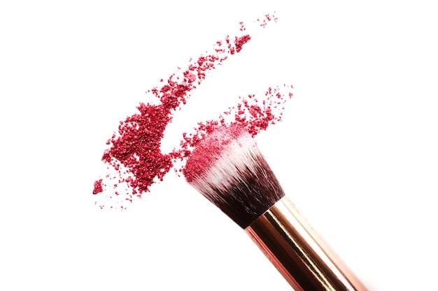 Fard à paupières écrasé avec pinceau de maquillage. isolé sur blanc. concept cosmétique. vue de dessus.