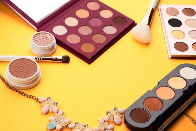 Fards à paupières professionnels et pinceaux de maquillage sur un maquillage jaune