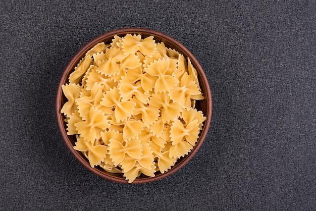 Farfalle ou bow tie pasta dans un bol sur un espace gris. pâtes italiennes