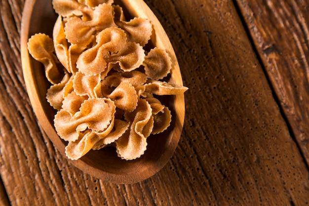 Farfalle crue ou pâtes noeud papillon sur cuillère en bois ,. pâtes intégrales sur une table en bois
