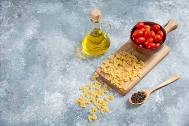 Farfalle crue, tomates et huile d'olive sur planche de bois.
