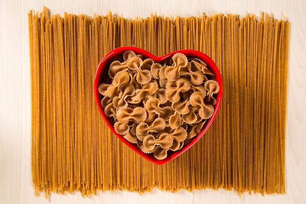 Farfalle intégral dans un bol coeur sur des spaghettis