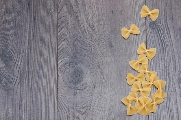 Farfalle italienne de pâtes crues italiennes non cuites sur fond en bois rustique.