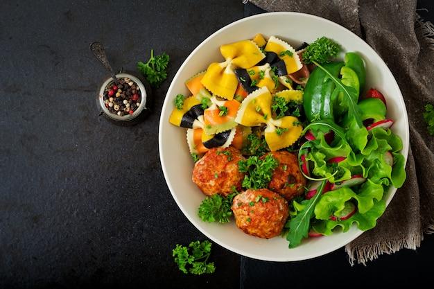 Farfalle pâtes blé dur avec boulettes de viande de filet de poulet au four à la sauce tomate et salade dans un bol.