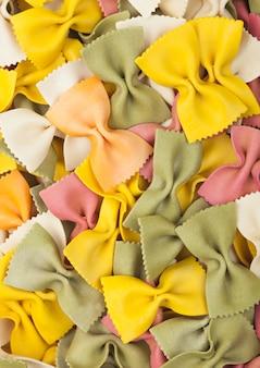 Farfalle pâtes de luxe italiennes multicolores comme fond de texture. vue de dessus