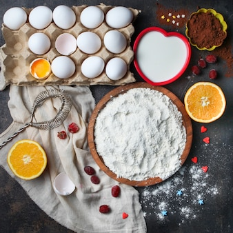 Farine aux œufs, orange, lait, cacao, fouetter dans un bol sur la surface en pierre