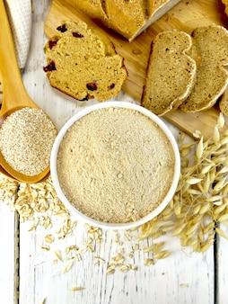 Farine d'avoine dans un bol blanc, son d'avoine en cuillère, flocons d'avoine et tiges, pain et biscuits sur fond de planches de bois sur le dessus