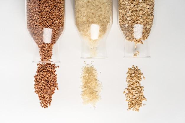 La farine d'avoine de riz sarrasin céréales renversé hors de récipients en verre sur un tableau blanc