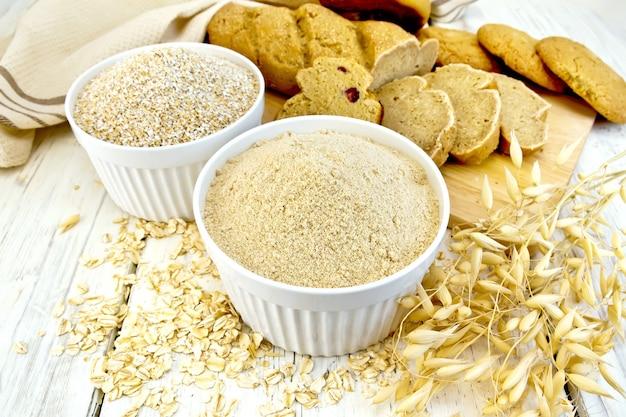 Farine d'avoine et son dans des bols blancs, flocons d'avoine et tiges, pain et biscuits, serviette sur fond de planches en bois