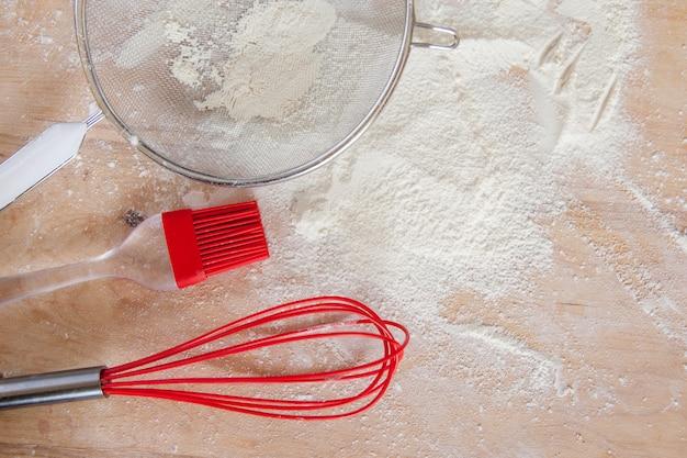 Farine blanche et outils en silicone rouge sur planche à découper en bois