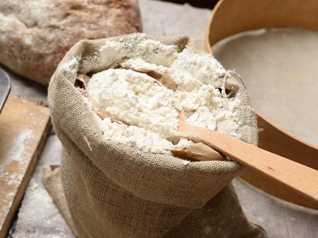 Farine de blé blanc dans un petit sac en toile de jute, close up