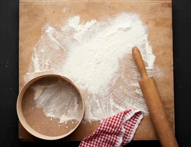 Farine de blé blanc éparpillée sur un tableau noir et un rouleau à pâtisserie en bois, tamis rond sur un tableau noir