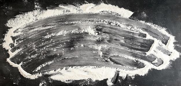 Farine de blé blanche dispersée sur un tableau noir