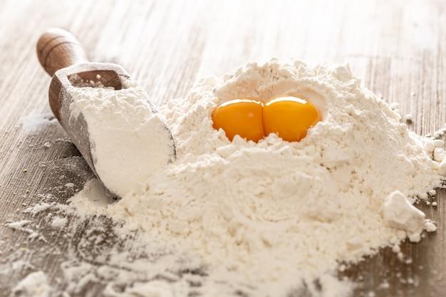 Farine de blé et œufs sur table de boulangerie prêts pour la préparation de pâte à gâteau ou de pâtes.