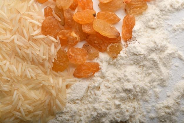 Farine, blé, riz, raisins secs et pièces de monnaie sur fond blanc