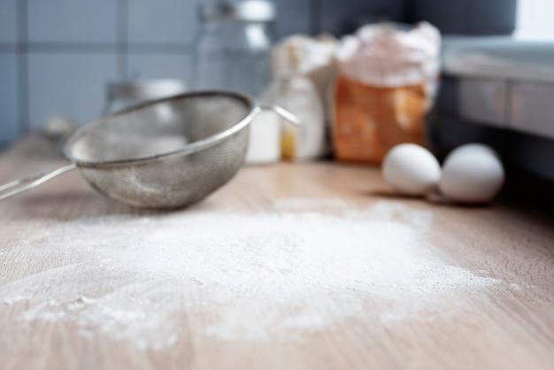 Farine de blé saupoudrée sur une table en bois dans la cuisine avec un tamis