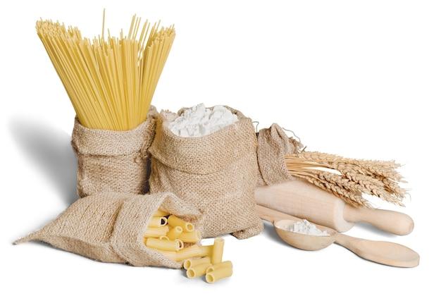 Farine, céréales, pâtes dans un sac en toile et oreille sur fond blanc
