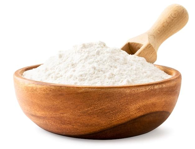 Farine dans une assiette en bois avec une cuillère gros plan sur fond blanc. isolé