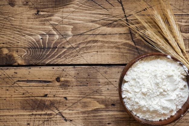 Farine dans un bol en bois et des épis de blé sur une table en bois.