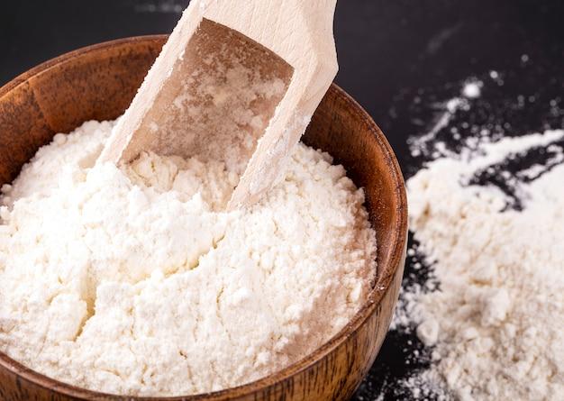 La farine dans un bol en bois et une pelle sur fond noir