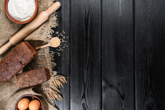 Farine dans un bol en bois sur une table en bois foncé avec des épillets de blé, des œufs et du lait, vue de dessus avec copie espace