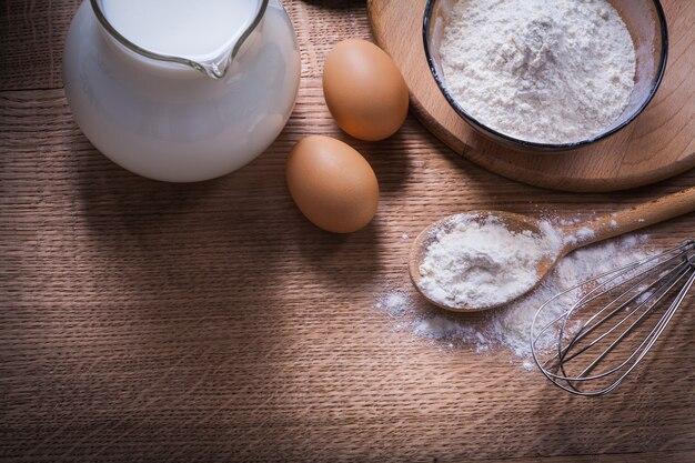 La farine dans un bol et une cuillère pichet corolle égout avec du lait sur bois